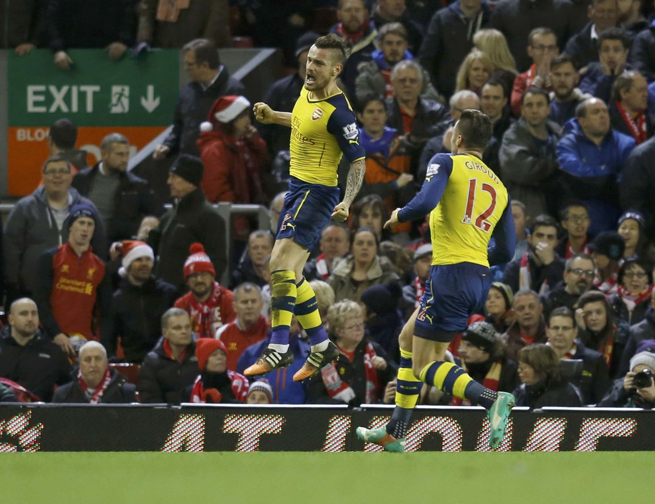 Arsenal's Mathieu Debuchy (L) celebrates after scoring a goal during their English Premier League soccer match against Liverpool at Anfield in Liverpool, northern England December 21, 2014. REUTERS/Phil Noble (BRITAIN - Tags: SOCCER SPORT) FOR EDITORIAL USE ONLY. NOT FOR SALE FOR MARKETING OR ADVERTISING CAMPAIGNS. EDITORIAL USE ONLY. NO USE WITH UNAUTHORIZED AUDIO, VIDEO, DATA, FIXTURE LISTS, CLUB/LEAGUE LOGOS OR 'LIVE' SERVICES. ONLINE IN-MATCH USE LIMITED TO 45 IMAGES, NO VIDEO EMULATION. NO USE IN BETTING, GAMES OR SINGLE CLUB/LEAGUE/PLAYER PUBLICATIONS. Foto: PHIL NOBLE/REUTERS