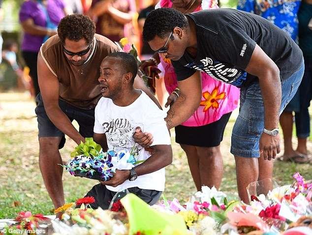 Gavin Willie, padre de cuatro de los ocho niños asesinados, se desplomó ante la ofrenda. Foto: Getty Images