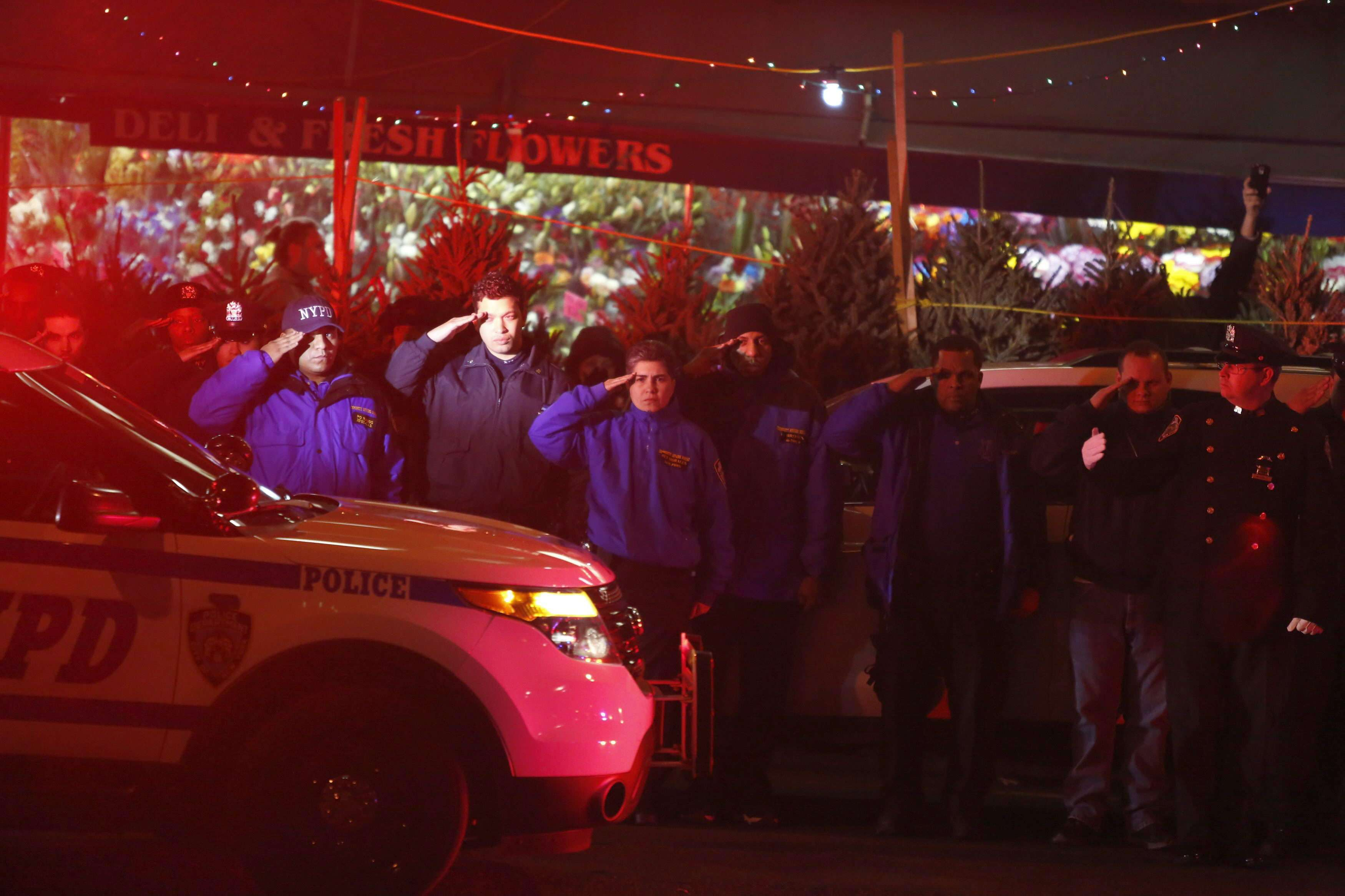 Oficiales de policía despiden, en los exteriores del Woodhull Hospital, a sus dos compañeros muertos. Foto: EFE en español