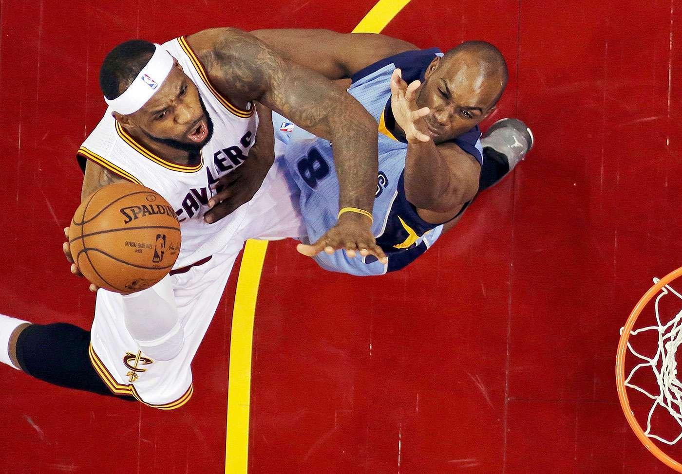 LeBron James, de los Cavaliers de Cleveland, dispara frente a Quincy Poindexter, de los Grizzlies de Memphis, en el encuentro del domingo 21 de diciembre de 2014 Foto: Mark Duncan/AP