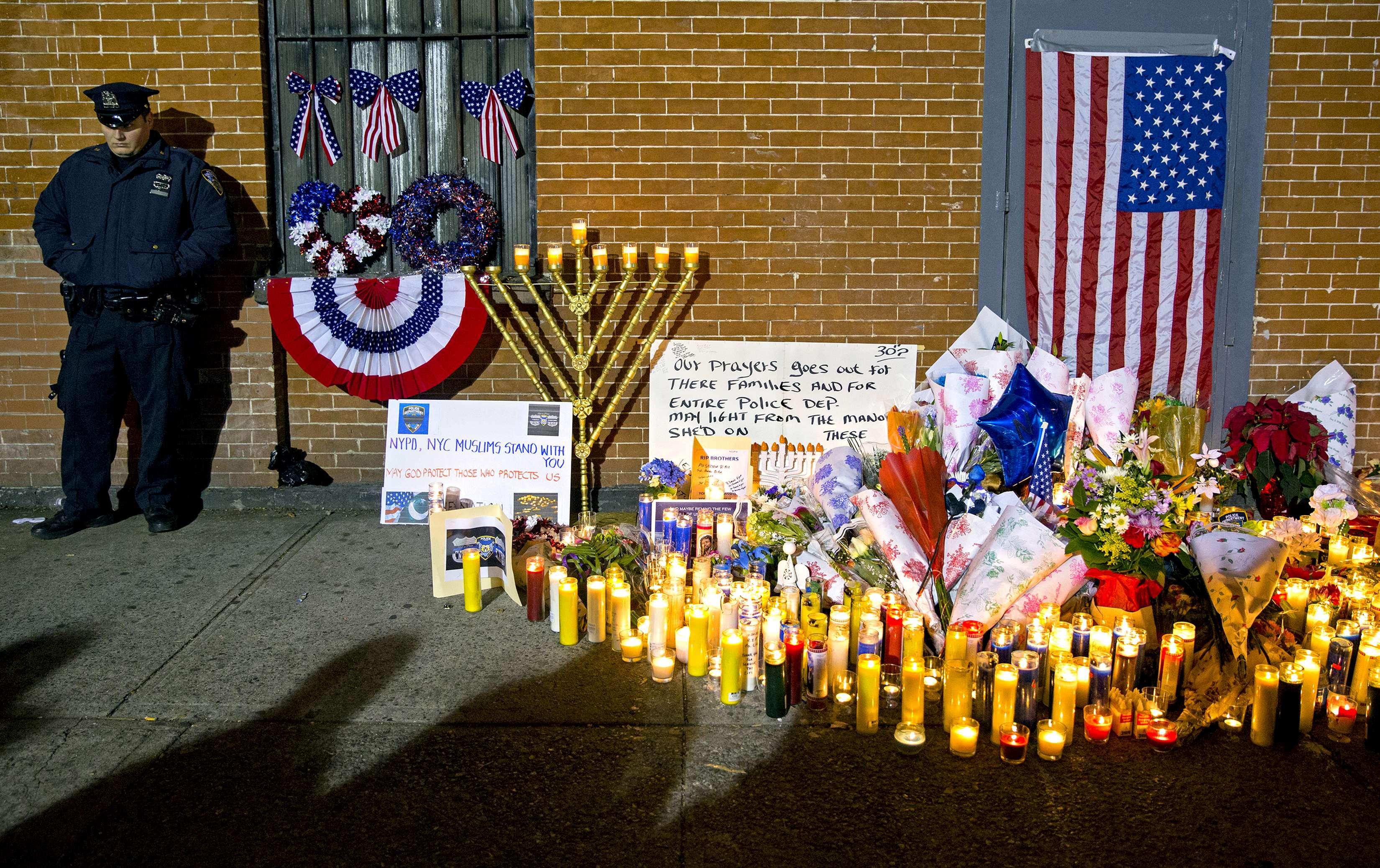 Un agente de la policía de Nueva York de pie junto a un punto donde la gente comenzó a depositar banderas, velas, mensajes y flores cerca del punto donde dos policías fueron asesinados el día antes, el 21 de diciembre de 2014. Foto: AP en español