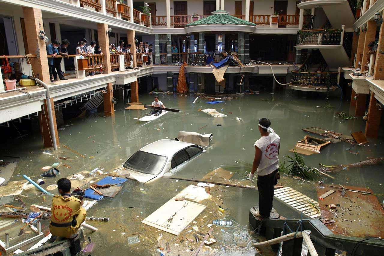 Equipos de rescatistas y de limpieza observan la entrada inundada del hotel Seapearl Beach Hotel, de Tailandia, tras el paso del tsunami que azotó la costa un par de días antes, 28 de diciembre de 2004. Foto: AP en español