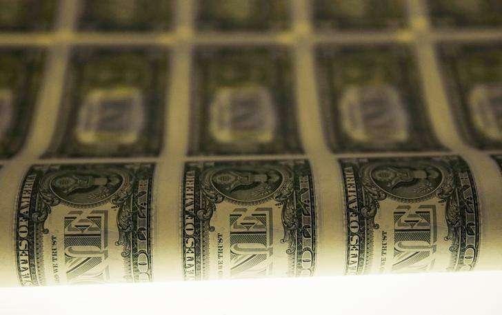 Una lámina de dólares americanos vista durante su etapa de producción en Washington. Imagen de archivo, 14 noviembre, 2014. Los inversores reducían sus posiciones en dólares en una sesión con pocos negocios el miércoles, lo que presionaba a la divisa estadounidense desde un máximo de casi nueve años luego de que sólidos datos económicos en Estados Unidos consolidaran las perspectivas de que la Fed elevará sus tasas de interés. Foto: Gary Cameron/Reuters