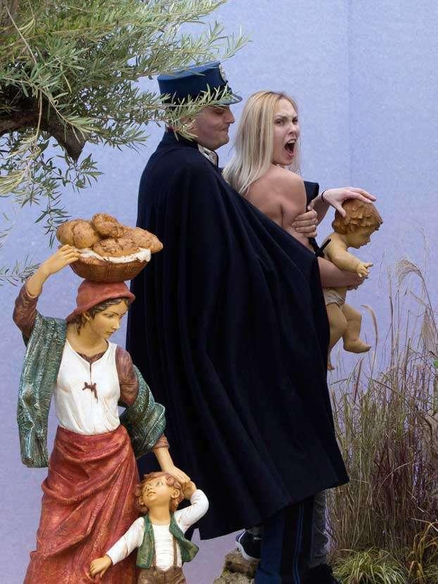 Una activista de Femen, supuestamente de Ucrania, trató de tomar la figura de tamaño natural del niño Jesús del nacimiento, belén, instalado en la Plaza de San Pedro, el Vaticano, pero fue capturada y arrestada por gendarmes y policías de la ciudad, el 25 de diciembre de 2014. Foto: AP en español