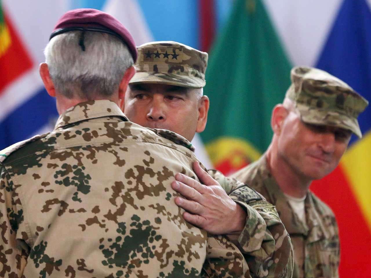 Los generales John Campbell y Hans-Lothar Domrose, de la ISAF, se abrazan durante la ceremonia que concluyó la operación de la OTAN y Estados Unidos en Afganistán, Kabul, el 28 de diciembre de 2014. Foto: AP en español
