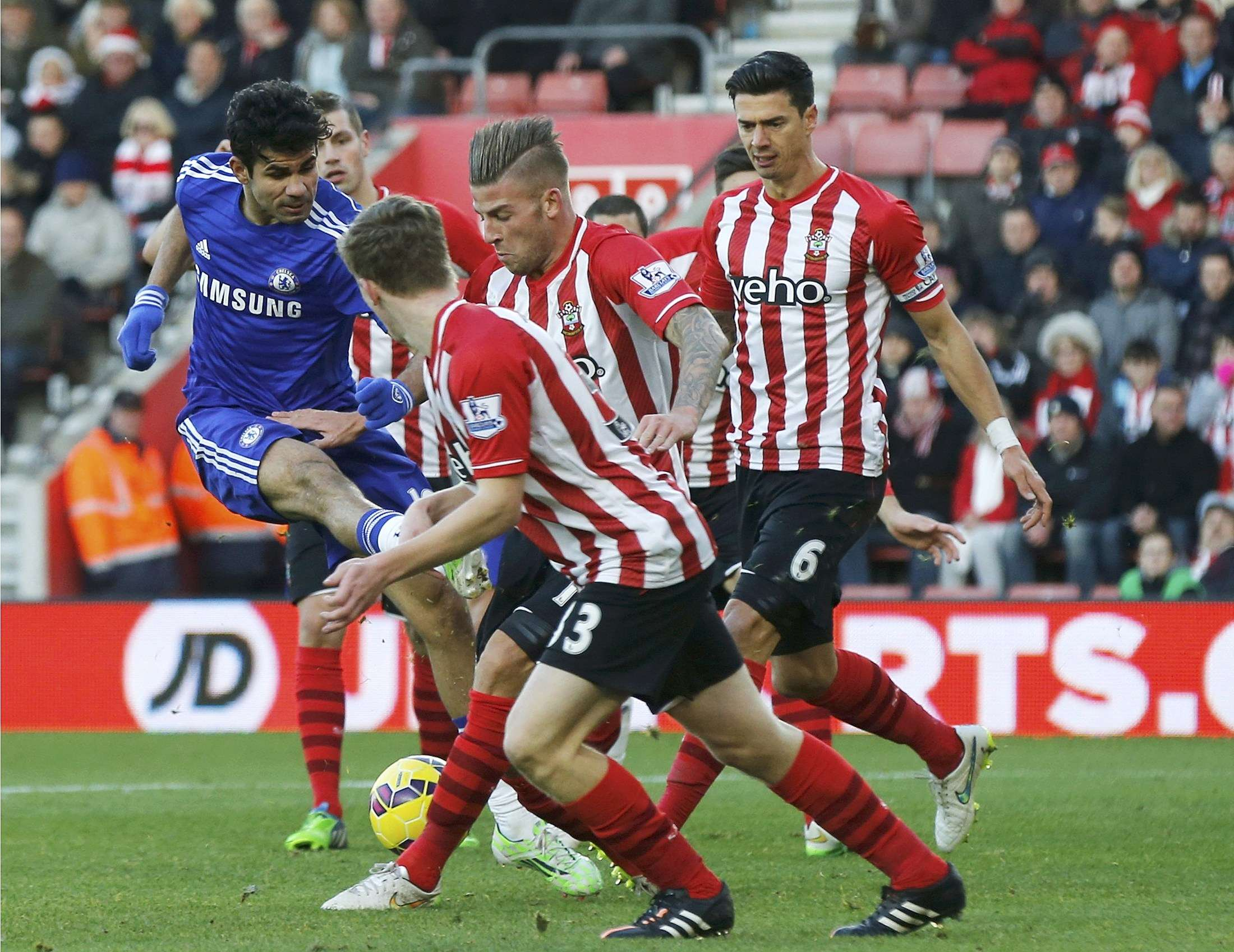 Diego Costa of Chelsea tries to shoot through a crowd of Southampton defenders during their English Premier League soccer match at St Mary's Stadium in Southampton, southern England, December 28, 2014. REUTERS/Suzanne Plunkett (BRITAIN - Tags: SPORT SOCCER) FOR EDITORIAL USE ONLY. NOT FOR SALE FOR MARKETING OR ADVERTISING CAMPAIGNS. EDITORIAL USE ONLY. NO USE WITH UNAUTHORIZED AUDIO, VIDEO, DATA, FIXTURE LISTS, CLUB/LEAGUE LOGOS OR 'LIVE' SERVICES. ONLINE IN-MATCH USE LIMITED TO 45 IMAGES, NO VIDEO EMULATION. NO USE IN BETTING, GAMES OR SINGLE CLUB/LEAGUE/PLAYER PUBLICATIONS. Foto: SUZANNE PLUNKETT/REUTERS