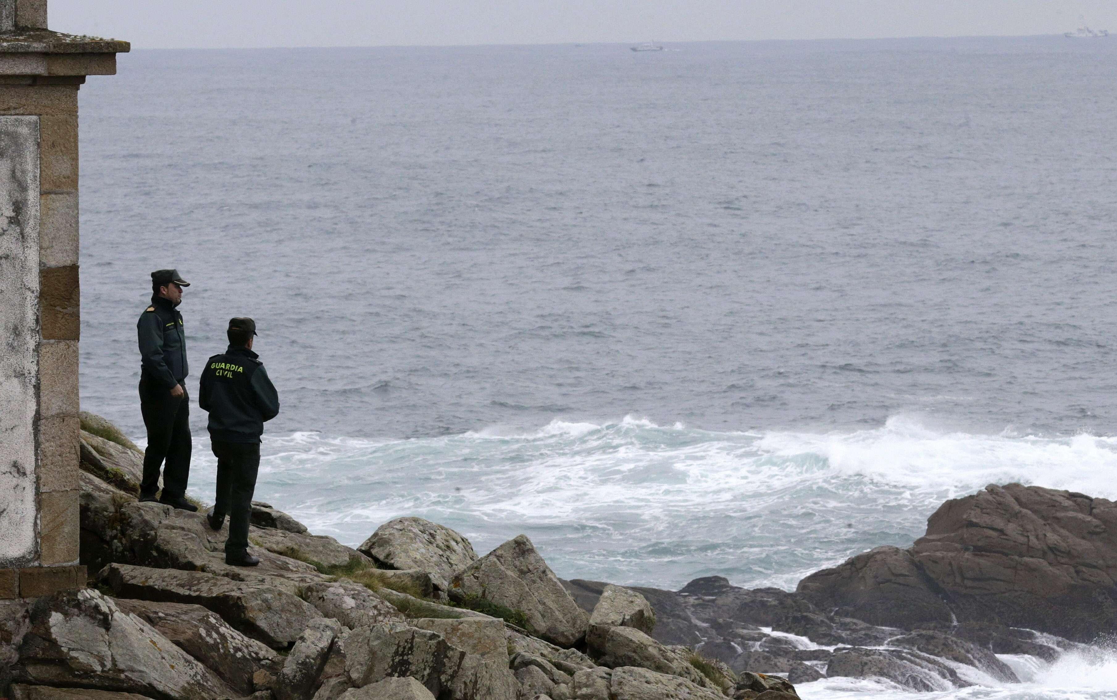 En la imagen, dos guardias civiles buscan por tierra a los dos desaparecidos del pesquero Paquito II, en las inmediaciones del faro de Corrubedo (19/12/2014). Foto: EFE en español