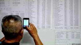 Homem olha lista de passageiros de voo desaparecido (foto: Getty) Foto: BBC Mundo/Copyright