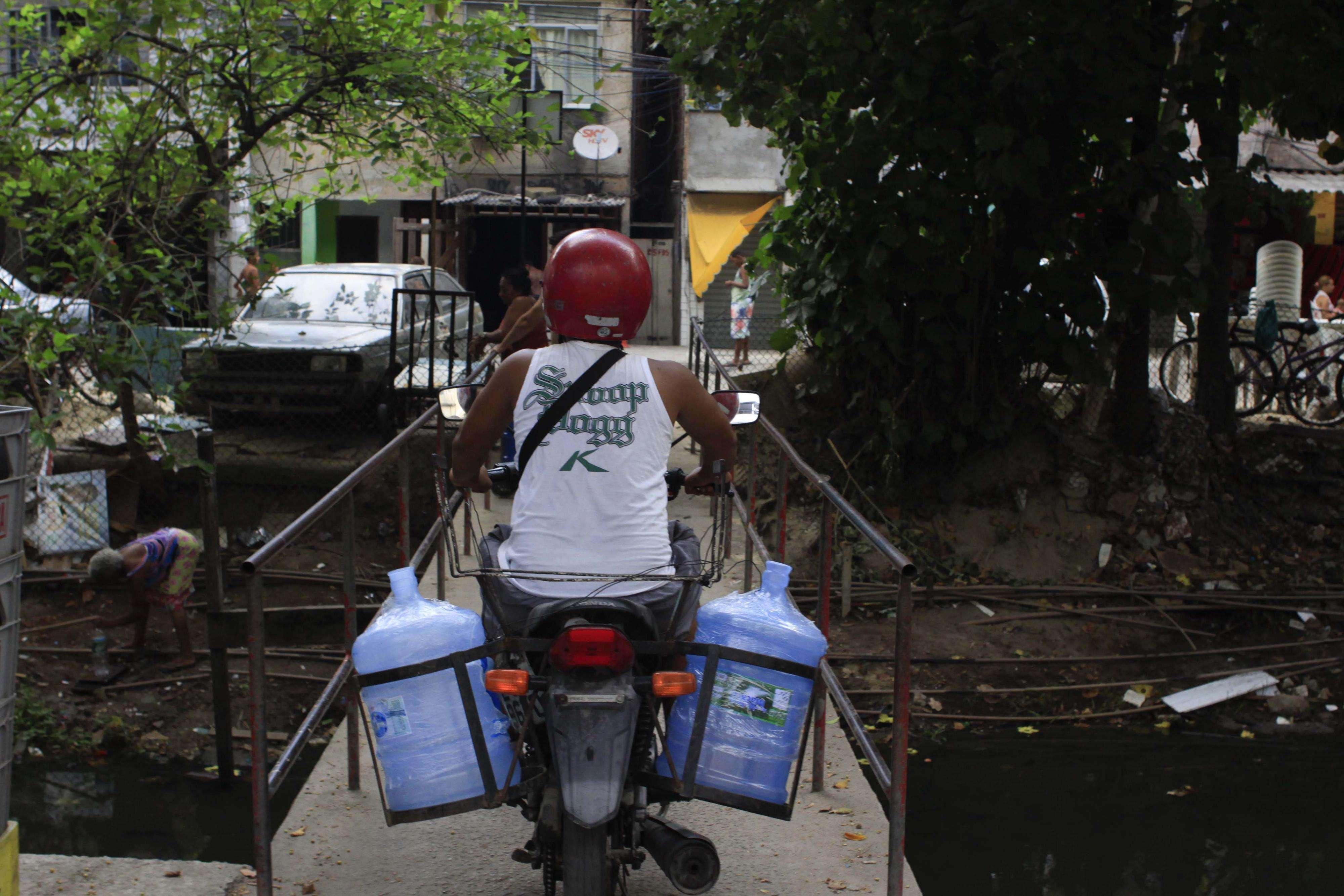 Moradores abastecem galões com água potável de uma bica no canal Foto: Ariel Subirá/Futura Press