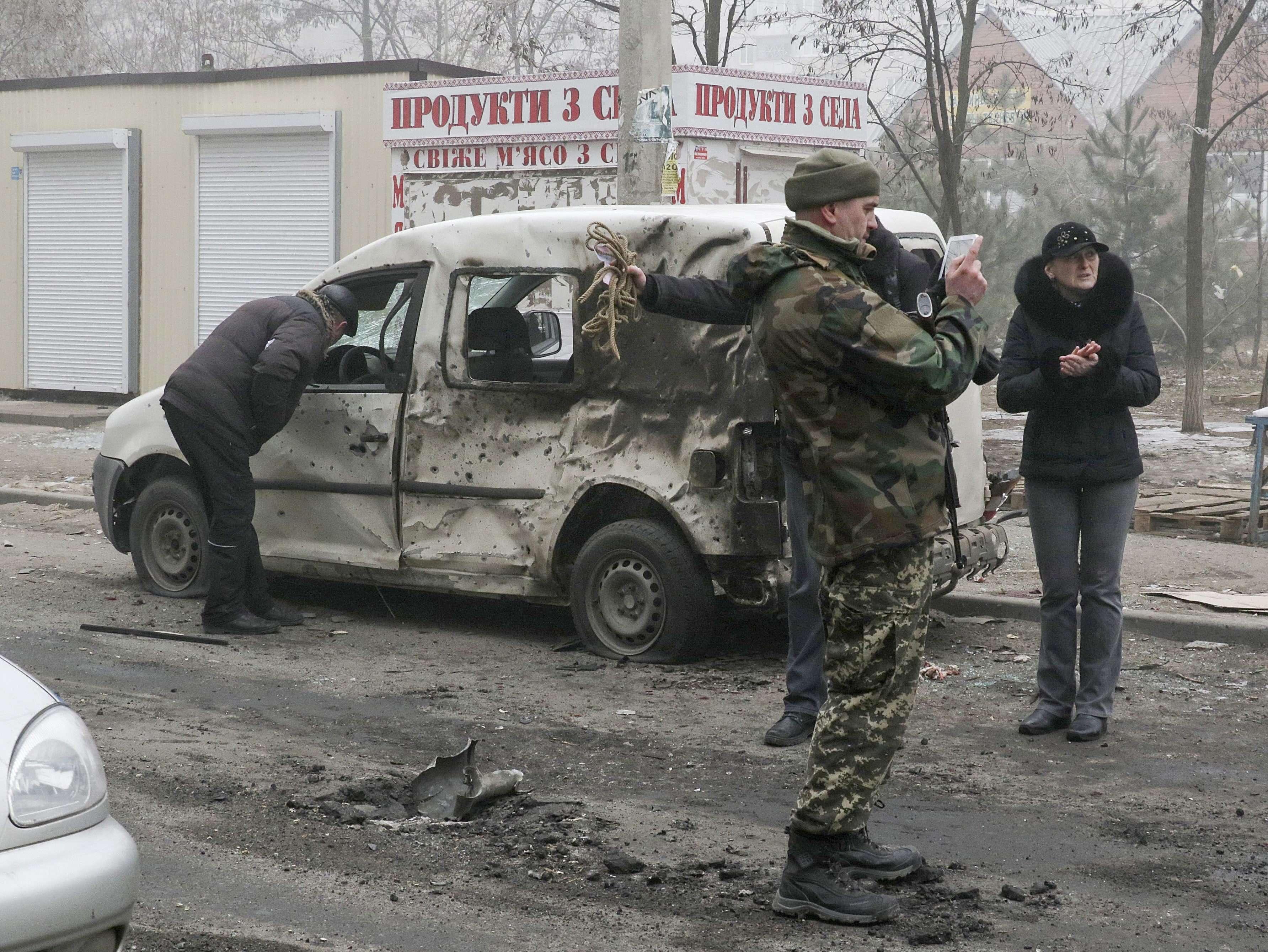 Militares ucranianos inspeccionan un coche dañado después de un bombardeo en la ciudad de Mariupol, en el este del país. Foto: EFE en español