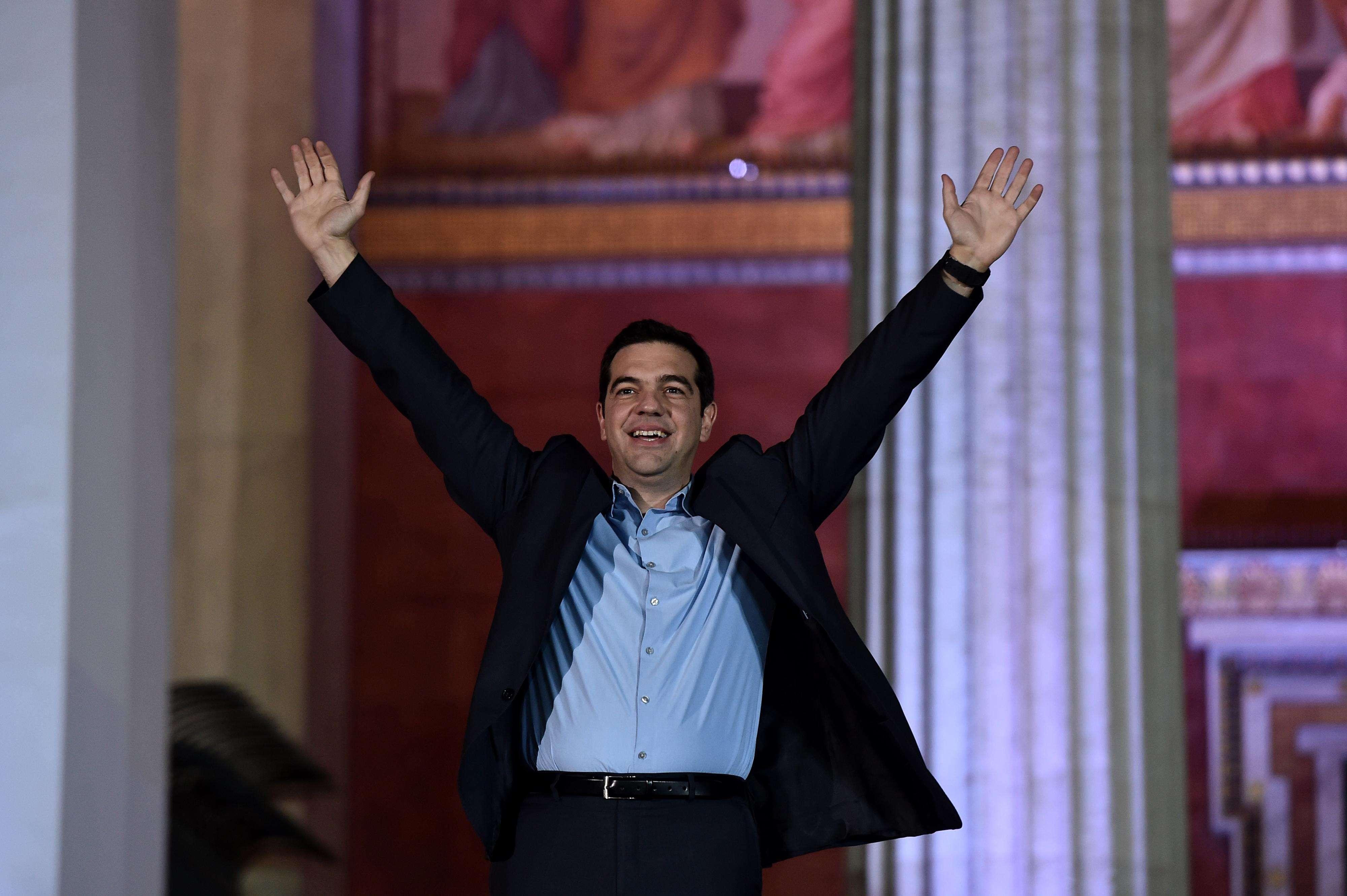 Alexis Tsipras, líder del partido de izquierda Syriza, levanta su puño en frente de la Academia de Atenas, tras la victoria en las elecciones generales griegas de este 25 de enero de 2015. Tsipras hizo campaña con la promesa de renegociar el país de internacional rescate y año inversas de recortes de gastos y reformas económicas dolorosas. Foto: AFP