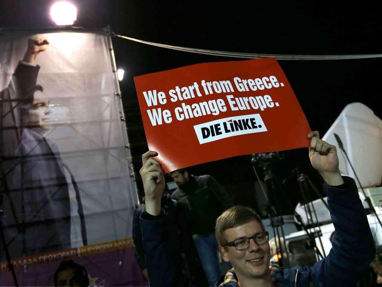 """Un hombre a las afueras de la casa de campaña de Syriza sostiene un cartel en el que se lee """"Empezamos en Grecia. Cambiamos Europa"""", 25 de enero de 2015. Foto: Reuters en español"""