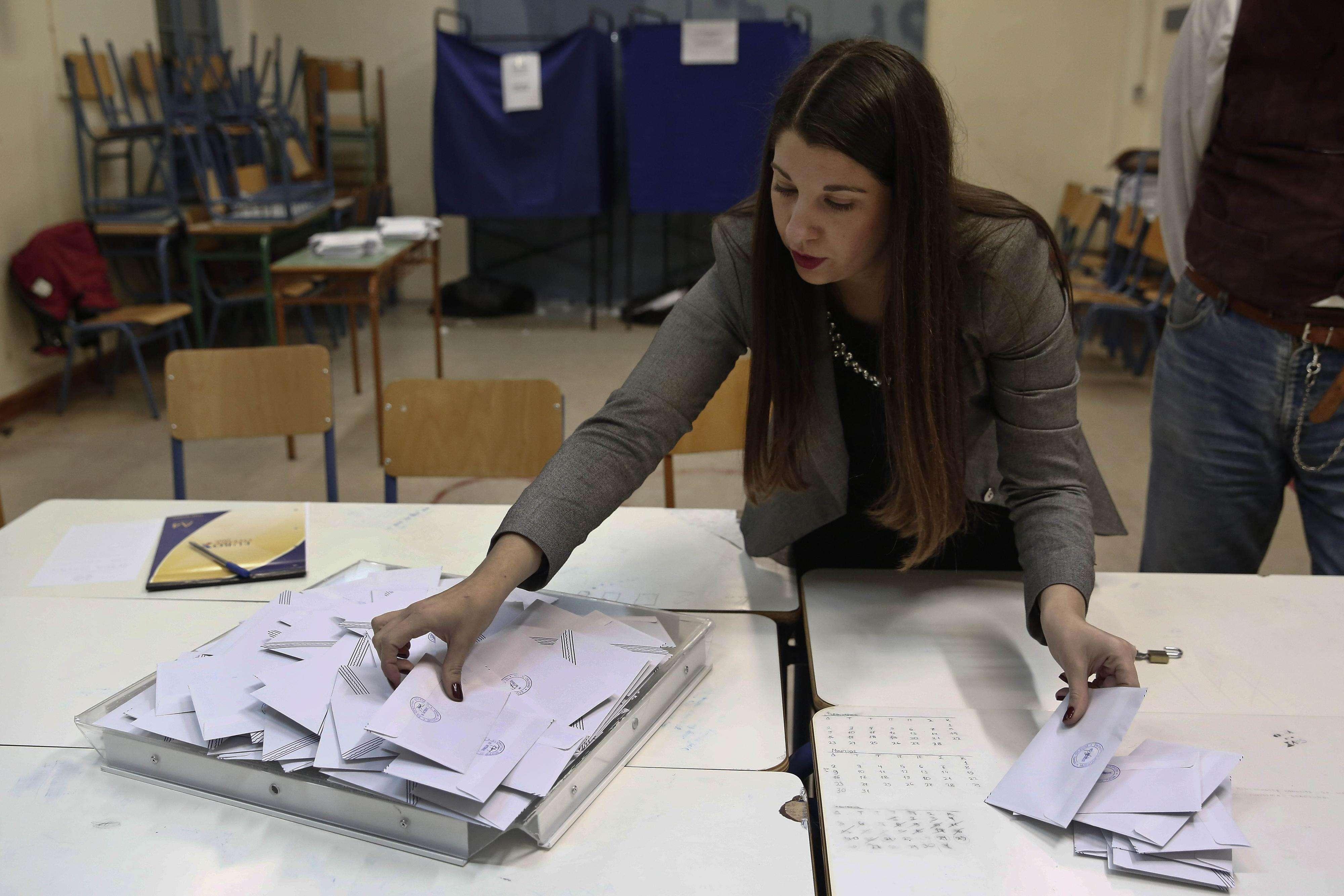 Funcionária conta cédulas em local de votação em Atenas, neste domingo Foto: Petros Giannakouris/AP