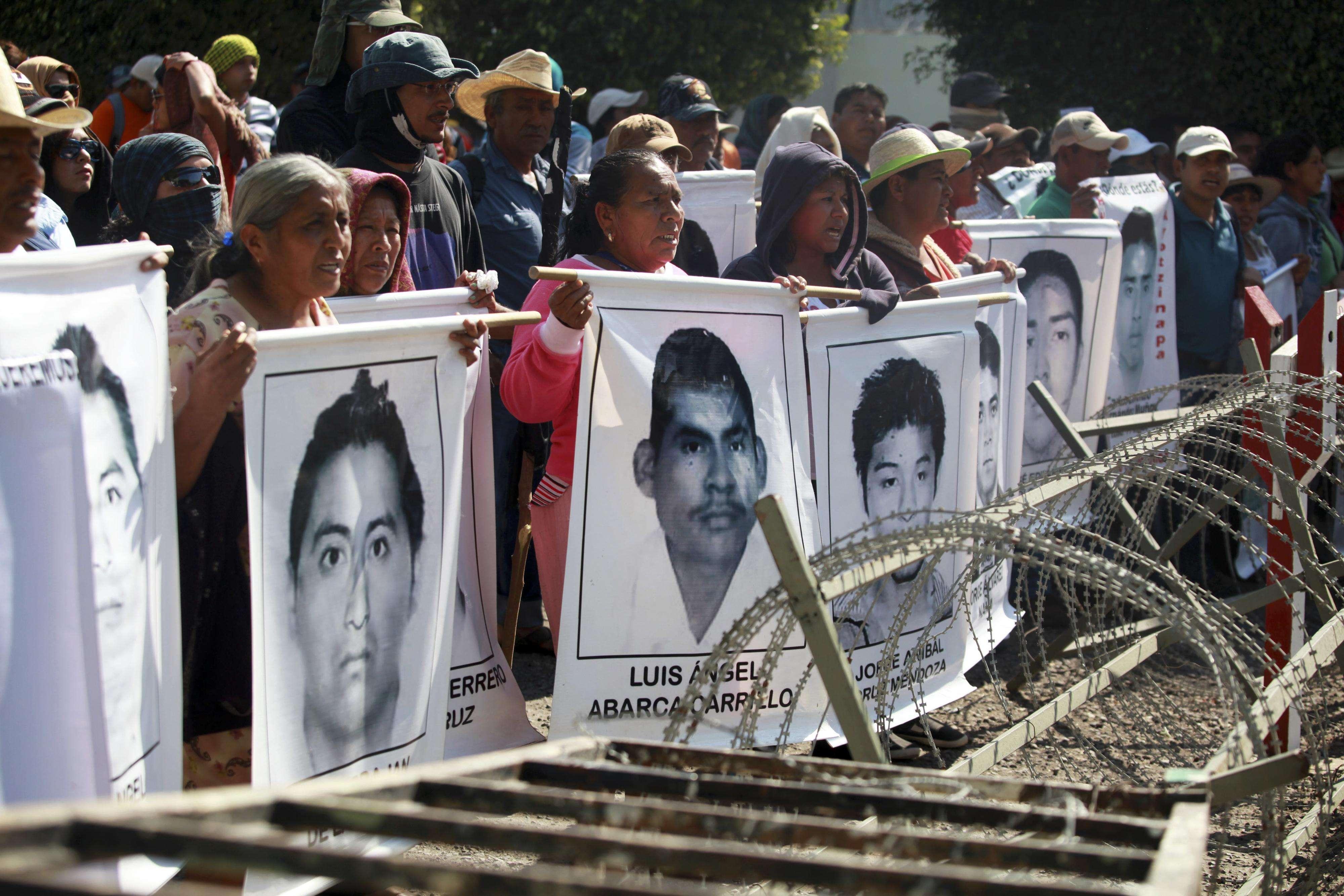 En esta foto de archivo del 18 de diciembre de 2014, parientes de estudiantes desaparecidos reclaman frente a la entrada del Batallón de Infantería 27 en Iguala, México. Foto: AP en español