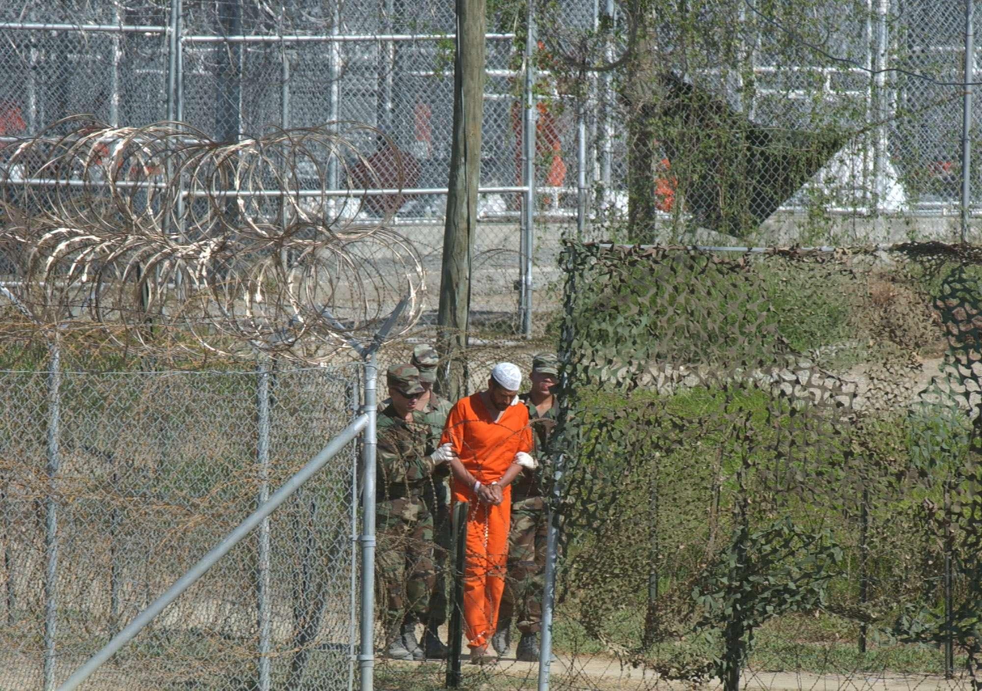 En esta imagen de archivo, tomada el 1 de marzo de 2002, un detenido es escoltado para su interrogatorio por policía militar en el campo X-Ray en la base naval estadounidense en la había de Guantánamo, Cuba. Foto: AP en español