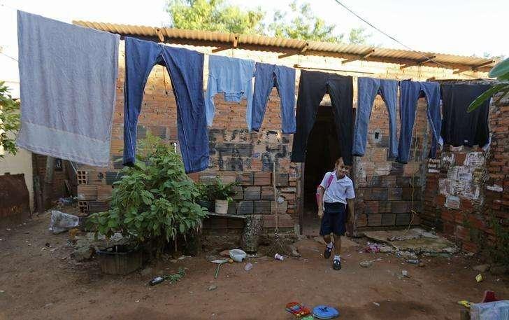 Una niña camina bajo ropa colgada para secar en su casa en Lambare, cerca de Asunción. Imagen de archivo, 2 abril, 2014. La pobreza afecta a un 28 por ciento de la población de América Latina, un nivel que mantiene desde el 2012, en medio de una desaceleración de la economía de la región, reveló el lunes la CEPAL en un informe. Foto: Jorge Adorno/Reuters