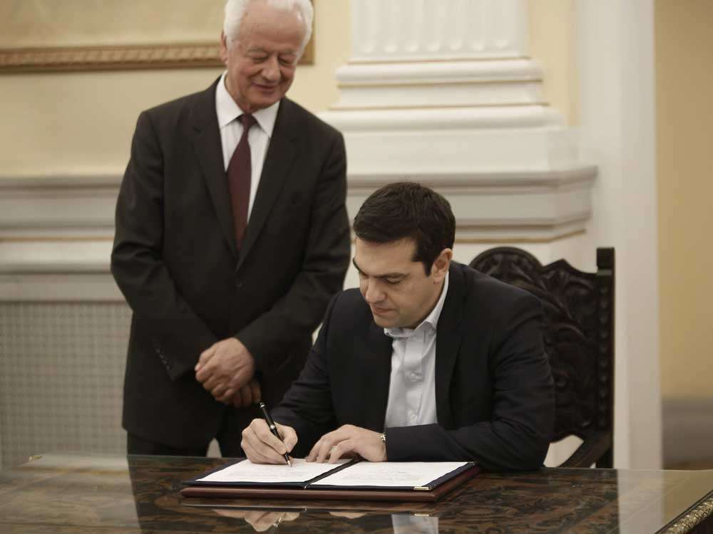 Alexis Tsipras firma un documento tras jurar como nuevo primer ministro griego. Foto: EFE en español