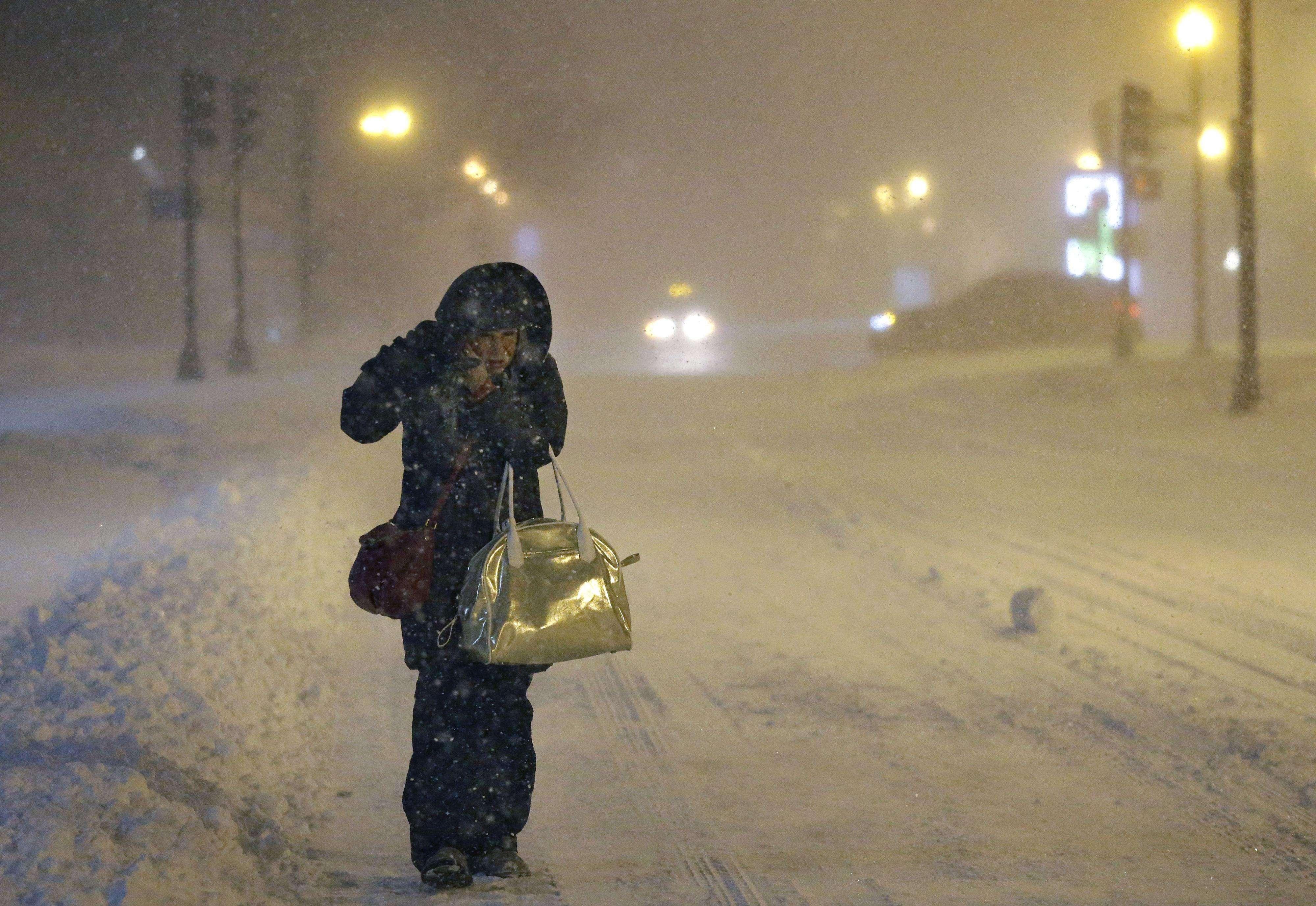 Denise Young, supervisora de enfermería en el Hospital General de Massachusetts, se acomoda su gorro mientras camina al trabajo en medio de una fuerte tormenta invernal, en Boston, el martes 27 de enero de 2015. Foto: AP en español