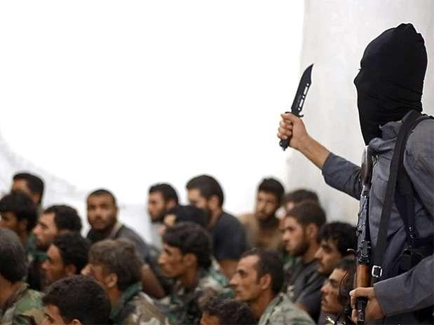 Un combatiente del grupo Estado Islámico, armado con un cuchillo y un arma automática, yace al lado de soldados sirios capturados y oficiales del ejército, en foto de archivo del 27 de agosto del 2014. Foto: AP en español