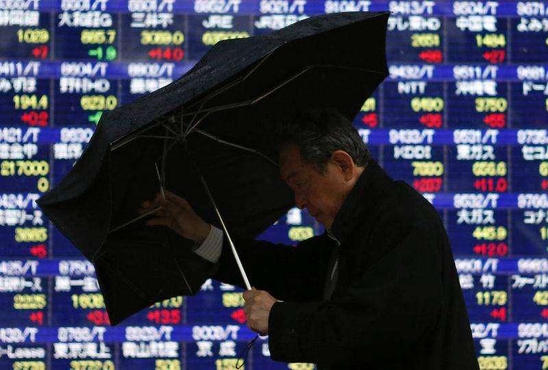 Un hombre observa una pantalla electrónica que muestra índices económicos en Tokio. Imagen de archivo, 6 enero, 2015. Las bolsas de Asia subían el miércoles mientras los inversores especulan si la Reserva Federal de Estados Unidos tomará un giro moderado en su comunicado al final de su reunión de política monetaria más tarde en la sesión, en medio de señales de que un fortalecimiento del dólar está debilitando las ganancias corporativas. Foto: Issei Kato/Reuters