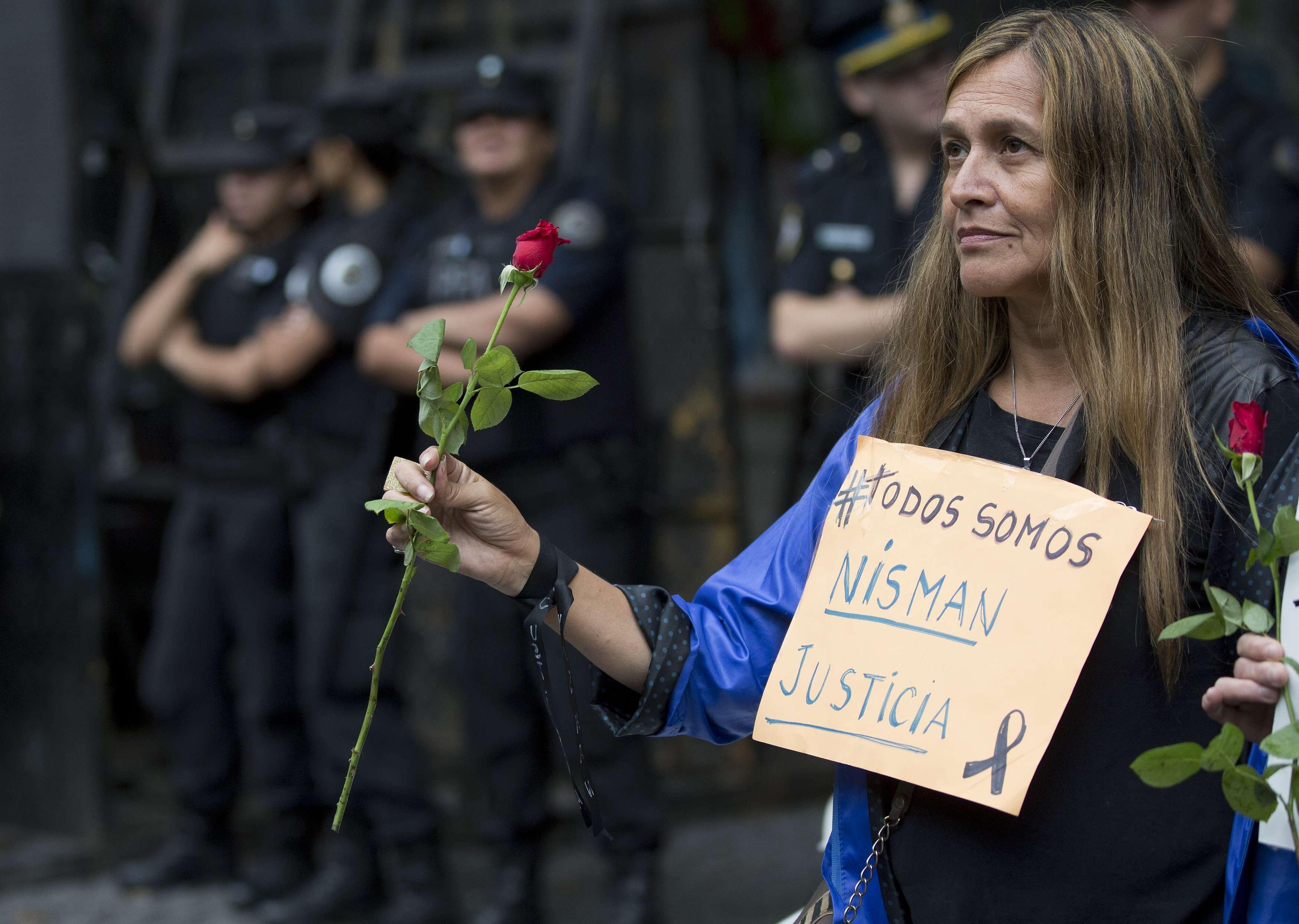 """Um homem carrega um cruz com a frase: """"Somos todos vítimas"""" em referência à misteriosa morte do promotor Alberto Nisman Foto: Rodrigo Abd/AP"""