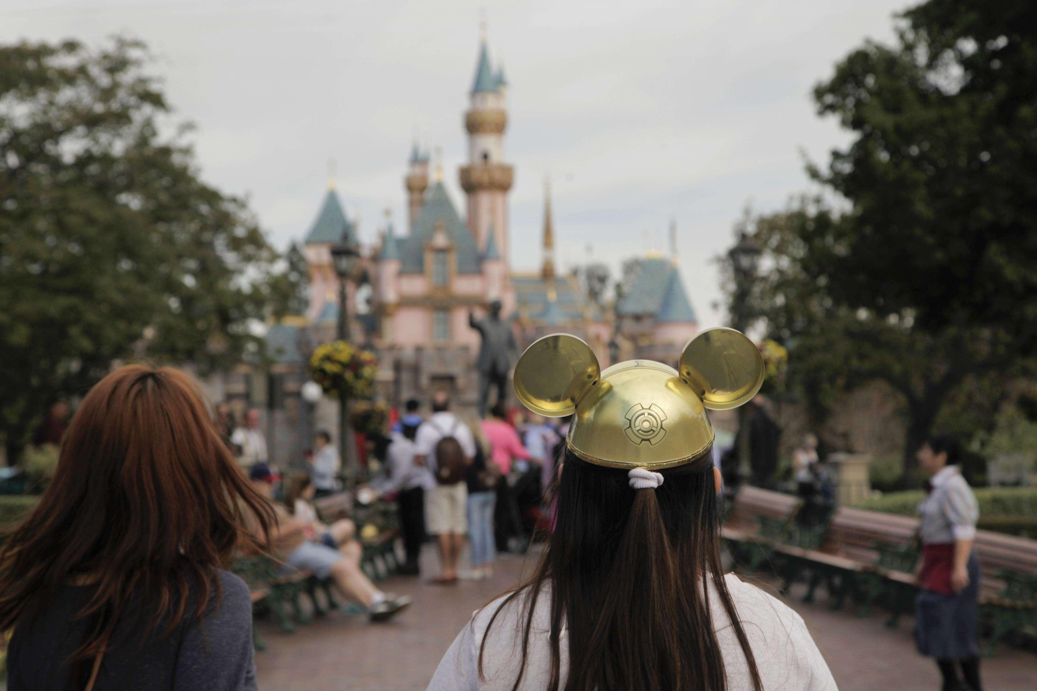 Una mujer con un gorro de Mickey Mouse camina hacia el Castillo de la Bella Durmiente en Disneyland el jueves, 22 de enero del 2015. Foto: AP en español