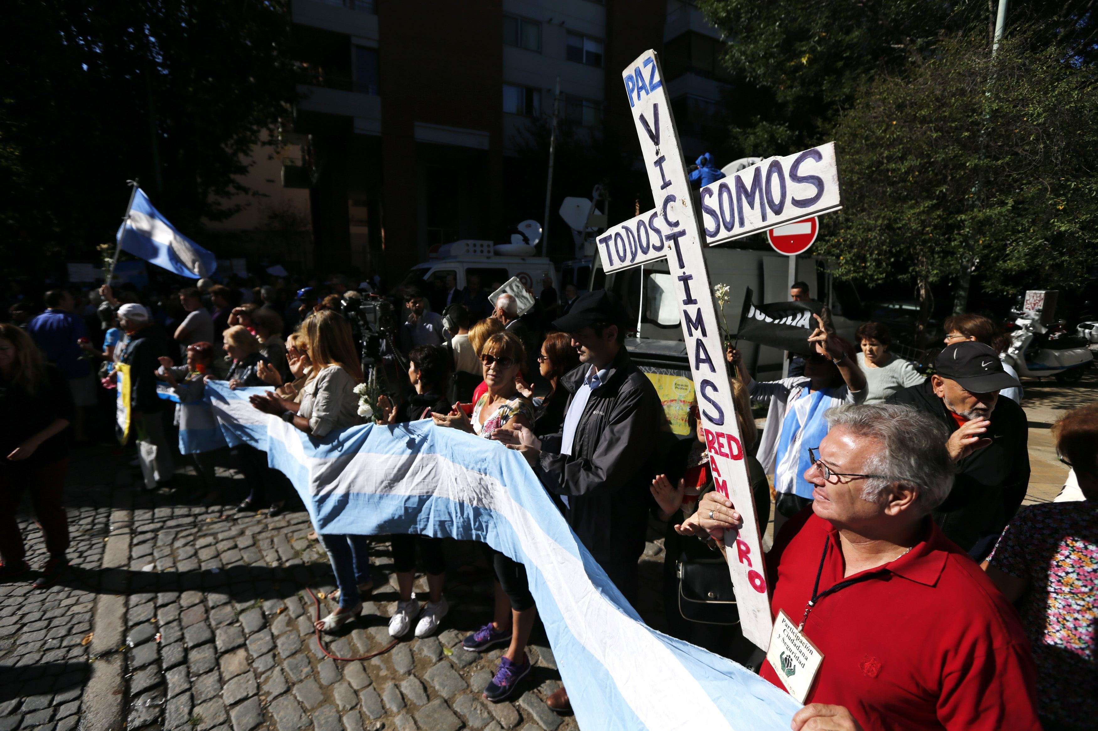 "A man holds a cross with words that read ""We are all victims"" as he waits for the hearse with the remains of late Argentine prosecutor Alberto Nisman in Buenos Aires January 29, 2015. The man who lent Argentine prosecutor Nisman the gun that killed him the day before he was to testify in Congress about allegations against the president emerged from hiding on Wednesday, saying the investigator feared for his family's life. Nisman's employee, Diego Lagomarsino, is the only person to be charged with any offence so far in the case of Nisman, who was investigating the 1994 bombing of Jewish community center in Buenos Aires. REUTERS/Marcos Brindicci (ARGENTINA - Tags: POLITICS CRIME LAW CIVIL UNREST OBITUARY) Foto: MARCOS BRINDICCI/REUTERS"
