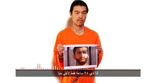 El periodista japonés Kenji Goto sosteniendo una foto del teniente jordano Muath al- Kaseasbeh. Foto: AP en español