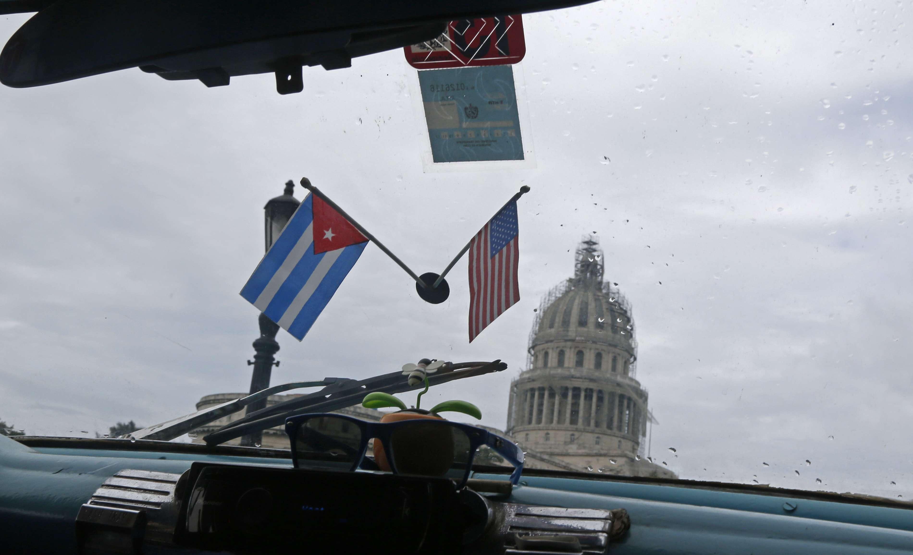 Banderitas de Cuba y Estados Unidos cuelgan del vidrio de un auto estadounidense clásico usado como taxi que pasa frente al Capitolio de La Habana el 16 de enero del 2015. Foto: AP en español