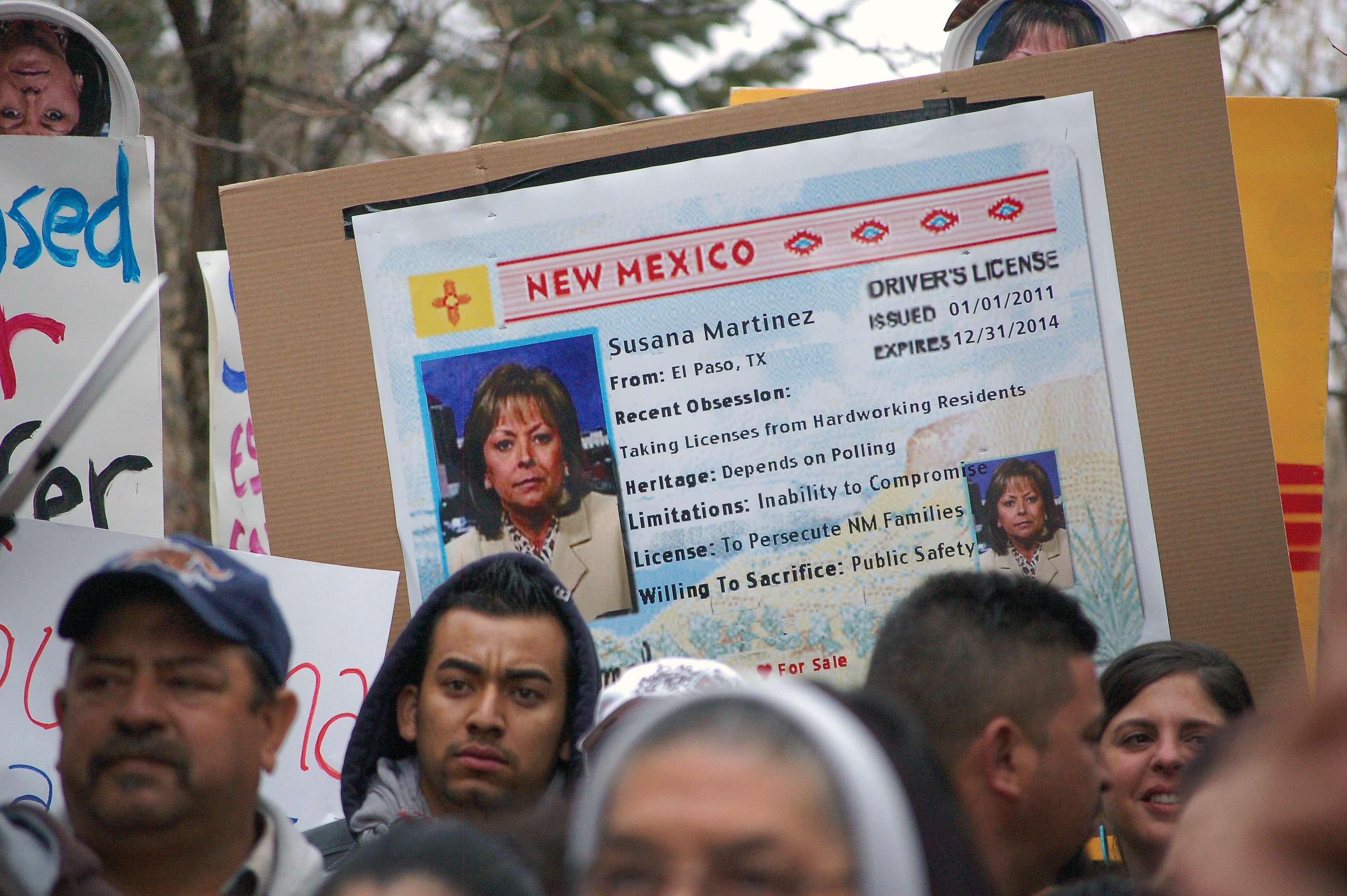 Defensores de los inmigrantes usan una imagen de la gobernadora Susana Martínez en una réplica de la licencia de conducir durante una protesta contra la propuesta de derogar una ley estatal que permite a indocumentados obtener ese documento. Foto: AP en español