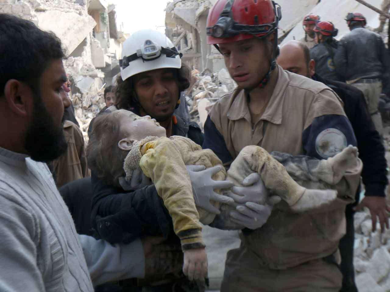 Trabajadores de rescate sacan a un niño de los escombros de una casa tras bombardeos del Gobierno sirio en la ciudad de Alepo, 1 de febrero de 2015. Foto: AFP en español