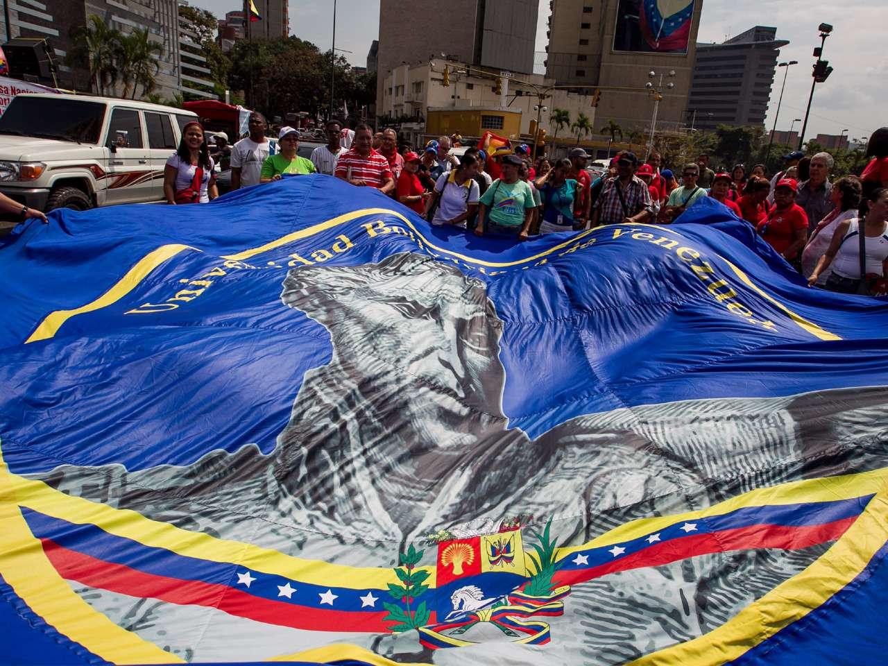 Manifestantes sostienen una bandera con la imagen de Simón Bolívar durante una movilización para conmemorar el 201 aniversario de la llamada Batalla de la Victoria, germen del nacimiento del Día de la Juventud en Venezuela, en Caracas. Foto: EFE en español