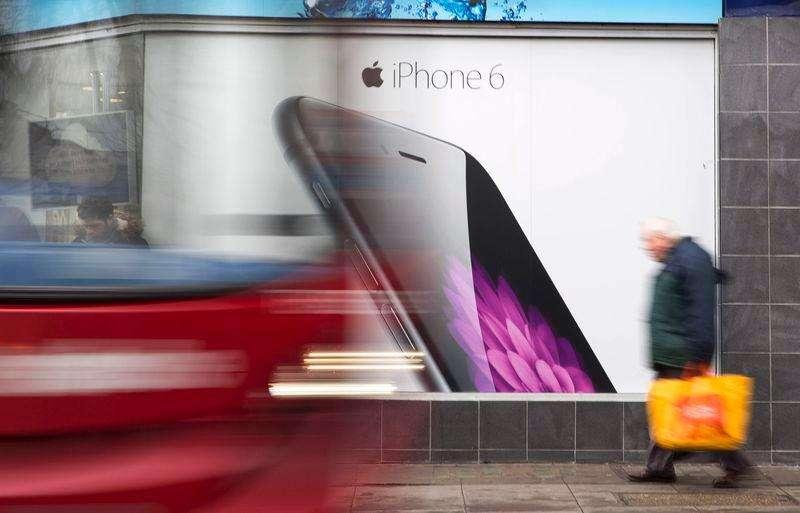 El inversor activista e importante accionista de Apple Inc Carl Icahn dijo que los títulos del fabricante del iPhone deberían cotizar a 216 dólares, muy por encima de su récord histórico de 124,92 dólares que alcanzaron el miércoles. En la imagen, un autobús y un peatón pasan junto a un anuncio del iPhone 6 en Londres, el 28 de enero de 2015. Foto: Neil Hall/Reuters
