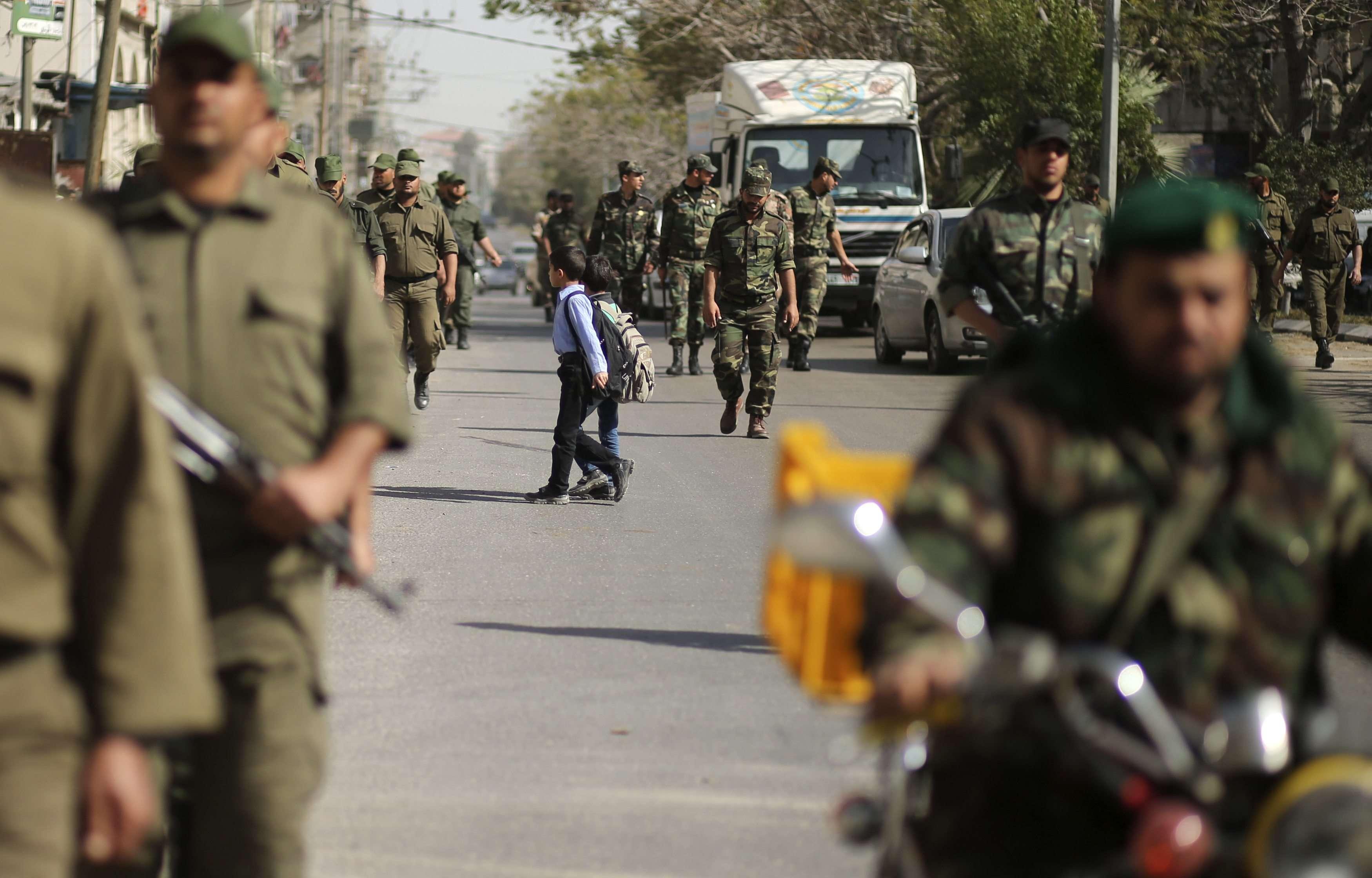 Crianças cruzam rua durante marcha de forças de segurança palestinas leais ao Hamas em Gaza, em 10 de fevereiro Foto: Reuters