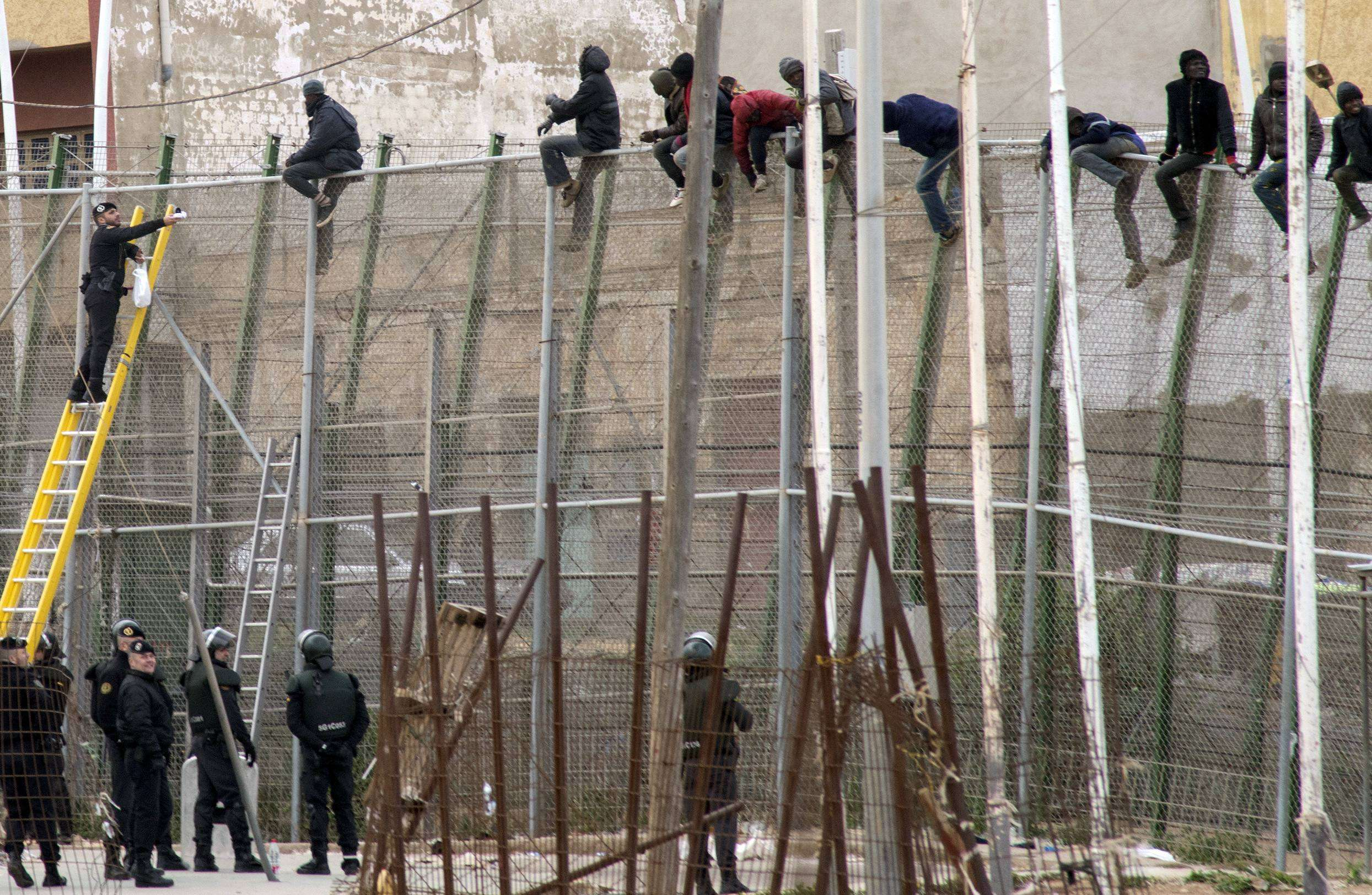 Inmigrantes encaramados a la valla de Melilla ante la mirada de varios agentes de la Guardia Civil Foto: Reuters