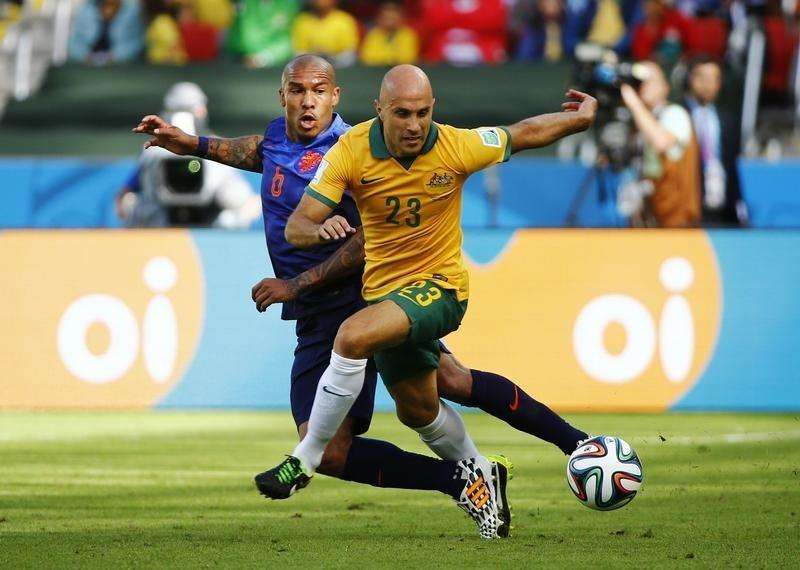 Nigel de Jong of the Netherlands (L) fights for the ball with Australia's Mark Bresciano during their 2014 World Cup Group B soccer match at the Beira Rio stadium in Porto Alegre June 18, 2014. Foto: Stefano Rellandini/Reuters