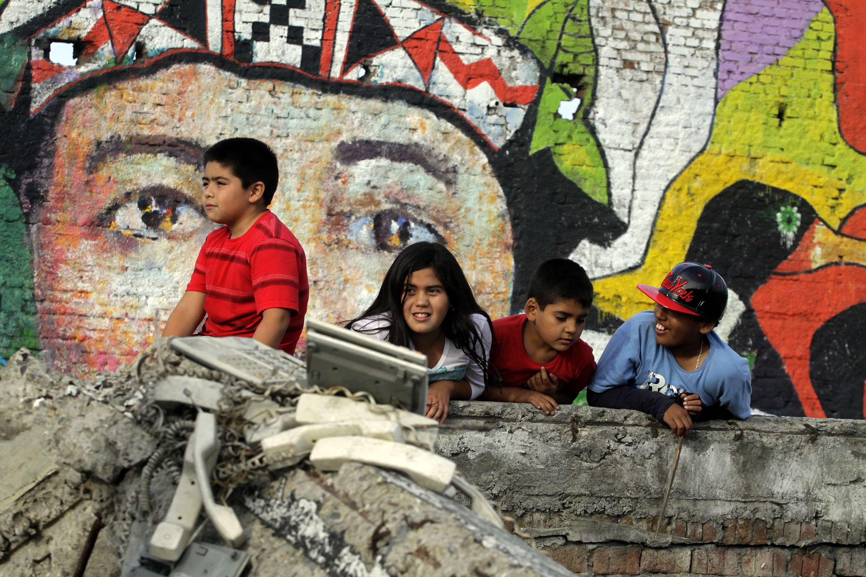 Niños juegan frente al recién inaugurado mural que recuerda el terremoto-maremoto del 27F en su quinto aniversario. El fatídico acontecimiento destruyó buena parte del centro civico de Talcahuano, base naval, estadio y muchas poblaciones del puerto. 27 de febrero de 2015. Foto: Agencia UNO