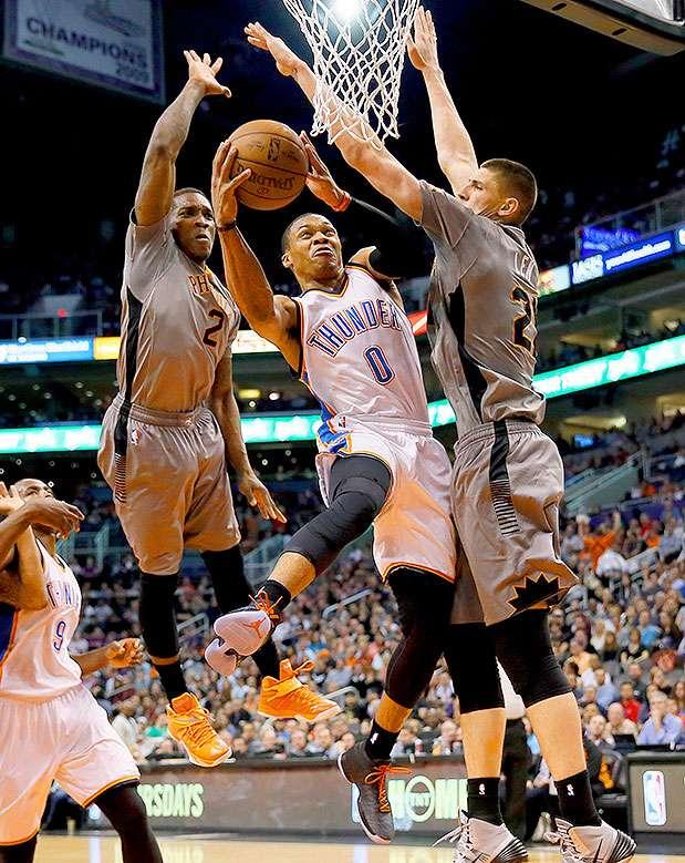 El jugador del Thunder de Oklahoma Russell Westbrook (0) lanza a canasta rodeado de los jugadores de los Suns de Phoenix Eric Bledsoe (2) y Alex Len (21) en la primera mitad de su partido de NBA, el 26 de febrero de 2015 en Phoenix. Foto: Matt York/AP