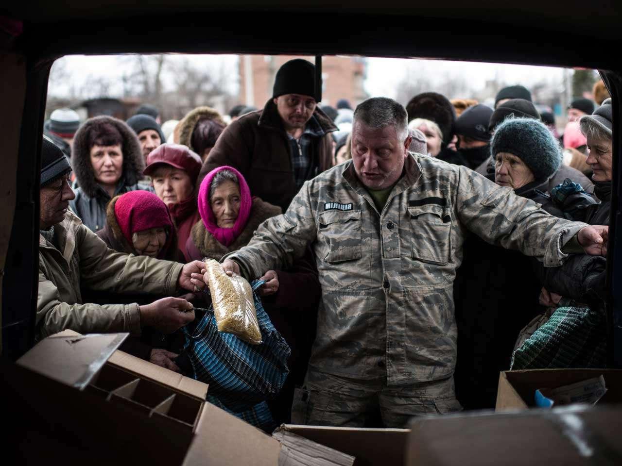 Un voluntario reparte ayuda humanitaria a residentes de Popasna, este de Ucrania, la tregua y el retiro de armamento da una esperanza para la paz en la región, 28 de febrero de 2015. Foto: AP en español