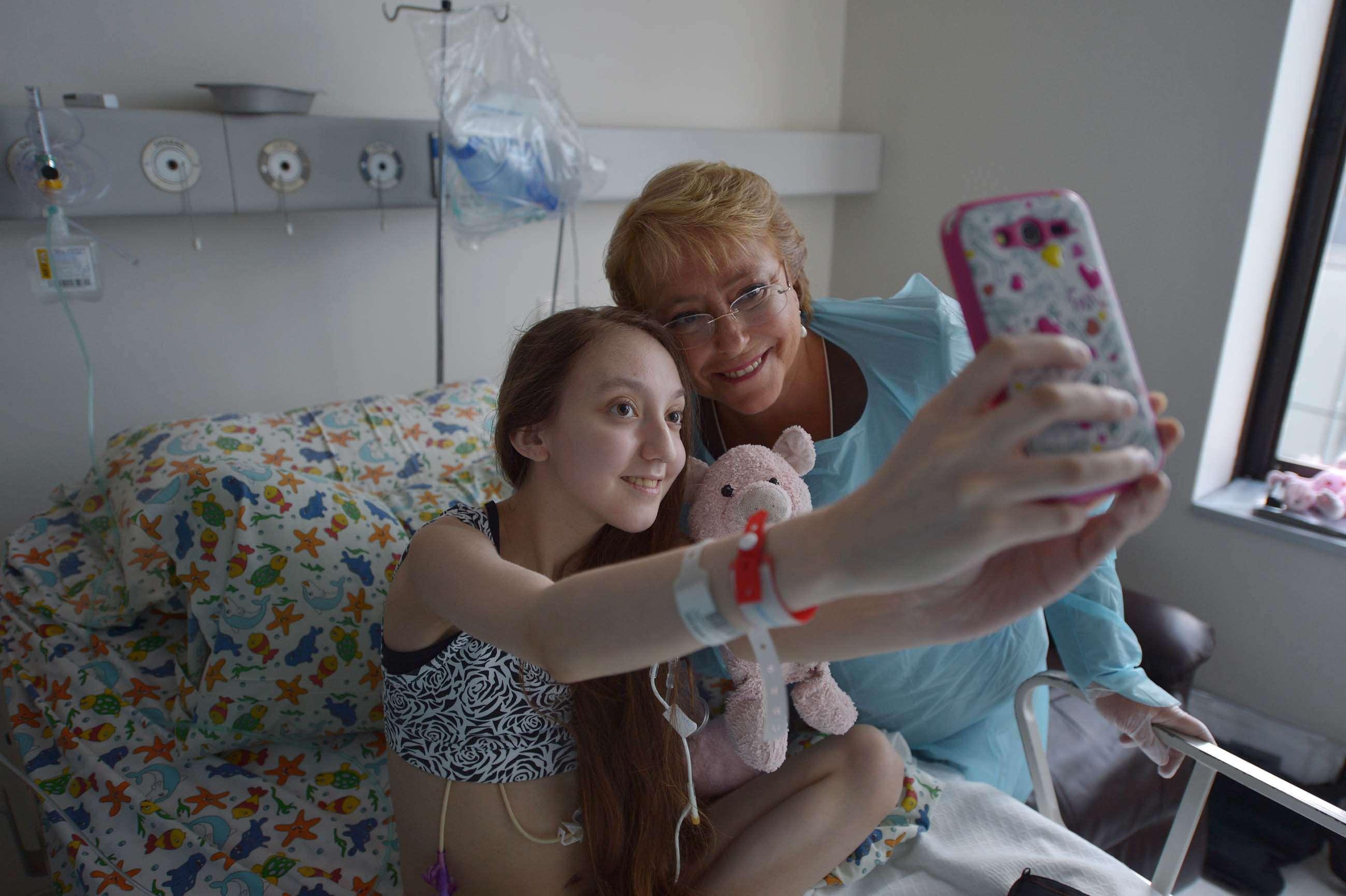 Bachelet estuvo este sábado más de una hora con Valentina Maureira en el hospital, donde también estaban los padres de la joven y la ministra de Salud, Carmen Castillo. Foto: EFE