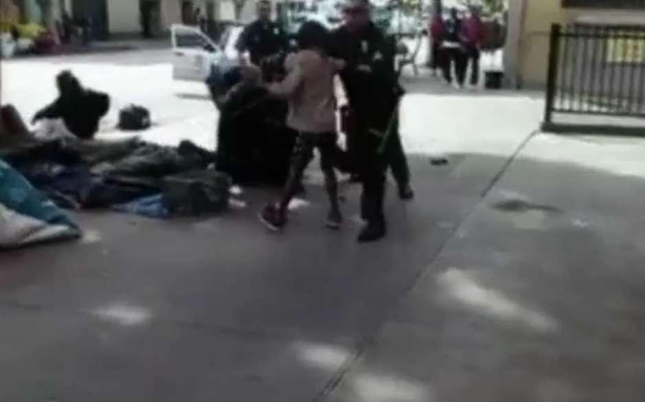 Vídeo feito por um observador mostra pelo menos quatro policiais lutando com o homem no solo ao lado do que parece ser uma série de lonas de plástico e sacos de dormir na calçada Foto: BBCBrasil.com