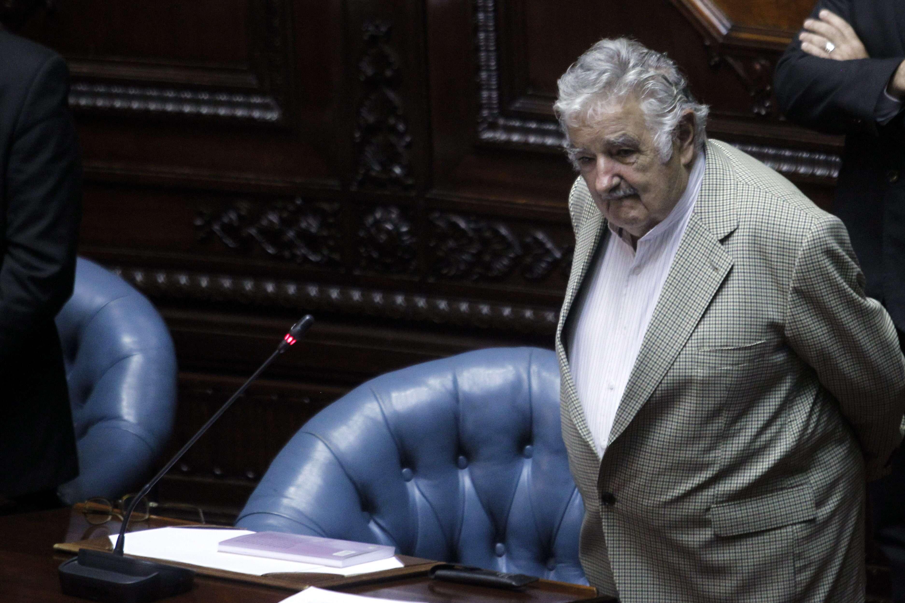 Mujica tuvo algún inconveniente a la hora de usar la tecnología para registrar el voto parlamentario, para lo que recibió ayuda de un funcionario. Foto: Hugo Ortuno/EFE