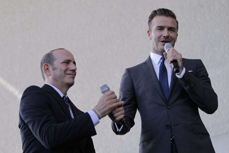 Don Garber (L) exchanges working microphones with David Beckham at a news conference in Miami, Florida February, 5, 2014. Foto: Andrew Innerarity/Reuters