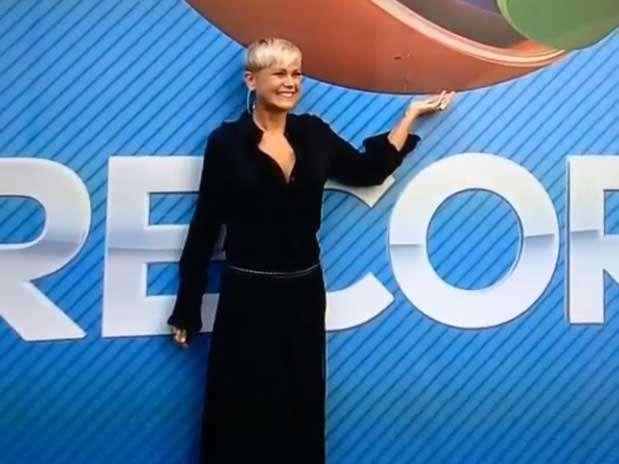 Xuxa sorri diante do logo da Record; em coletiva, apresentadora fala do novo desafio Foto: Instagram/Reprodução