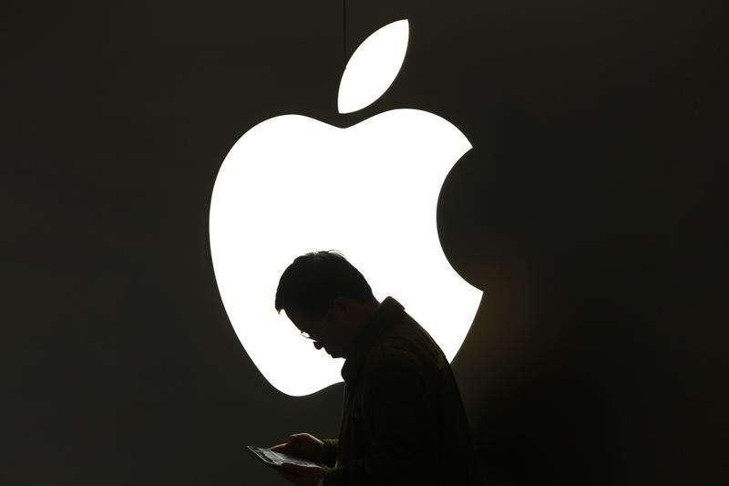Apple Inc postergará el inicio de la producción de un iPad de pantalla más grande, de 32,7 centímetros, hasta alrededor de septiembre debido a problemas relacionados con el suministro de pantallas, dijo Bloomberg News según fuentes con conocimiento de los planes de la compañía. En la imagen de archivo, un hombre mira su iPad frente a un logo de Apple en el centro ede Shanghai el 16 de marzo de 2012. Foto: Aly Song/Reuters