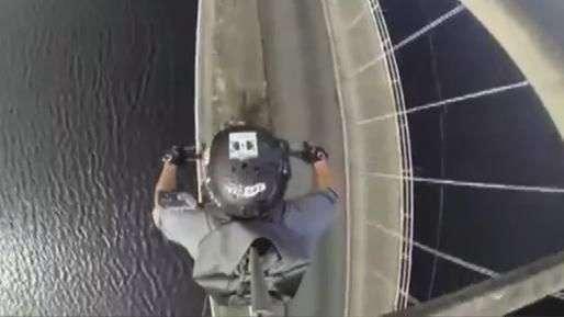 Homem desafia perigo ao passar de moto sobre arco de ponte