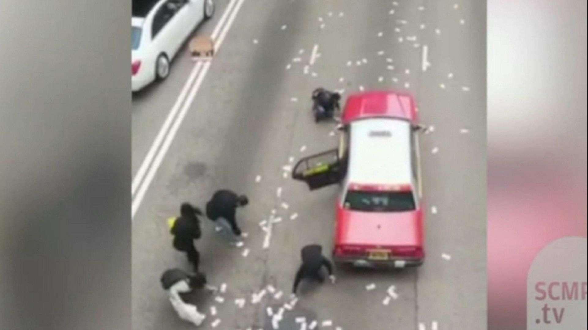 Pedestres correm para pegar dinheiro que caiu de carro forte