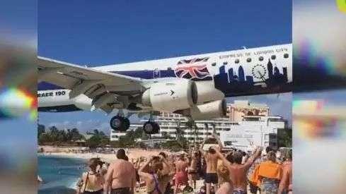 Banhistas filmam avião que passa a metros sobre praia cheia