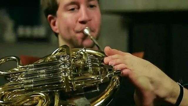 El músico que toca la trompa con sus pies