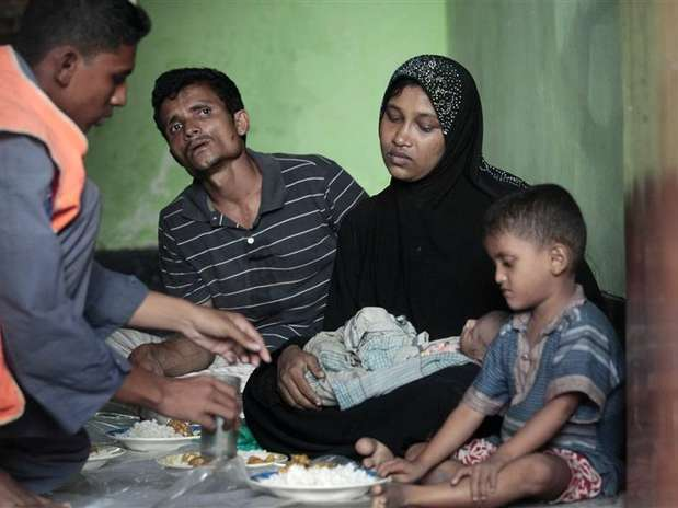 A member of the Bangladesh Coast Guard serves food to Mohammad Rafique and Amena Akter, both Rohingyas from Myanmar, in Teknaf June 19, 2012. Foto: Andrew Biraj / Reuters